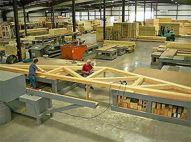 Large roof timber frame trusses are pre-assembled by skilled craftsmen