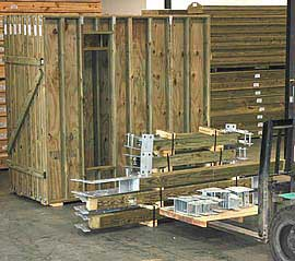 Prepackaged treated lumber walls and structural components with galvanized steel couplings staged and ready for shipment.